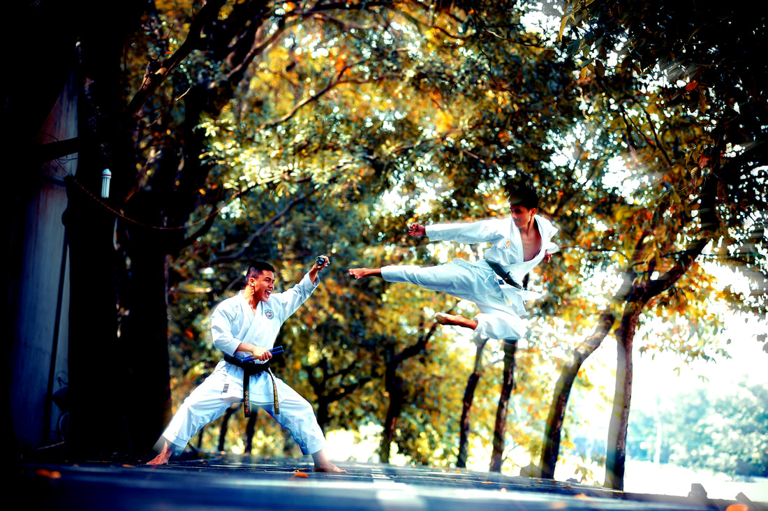 Two men in karate uniforms fighting.
