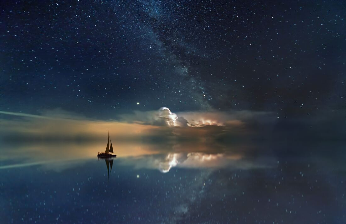 Black sailboat on smooth water reflecting the night sky